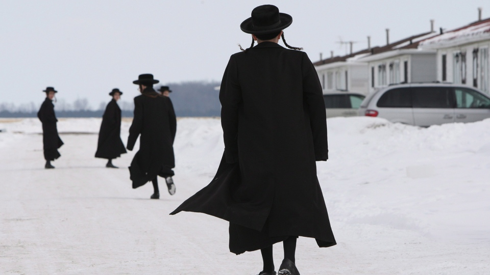 Members of the Lev Tahor ultra-orthodox Jewish sect walk down a street while an emergency motion in the child custody case is held at the courthouse in Chatham, Ont., Wednesday, March 5, 2014. (THE CANADIAN / Dave Chidley)