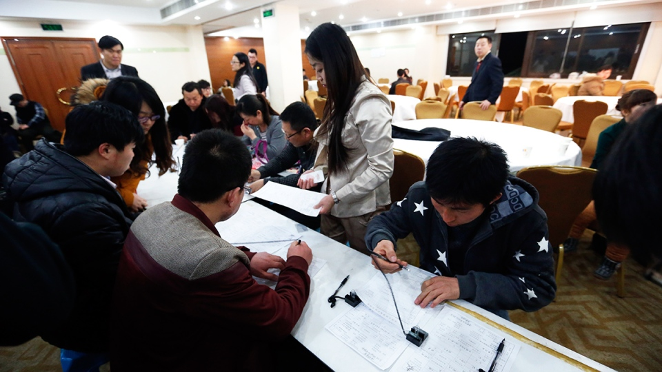 Chinese relatives of passengers aboard a missing Malaysia Airlines plane fill out passport forms at a hotel for relatives or friends of passengers aboard the missing airplane, in Beijing, China, Sunday, March 9, 2014. (AP / Vincent Thian)
