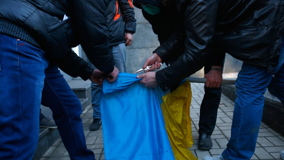 Pro Russia protestors work to remove a Ukrainian flag from a flagpole which they took from the regional governance Security Service of Ukraine building during a rally in Donetsk, Ukraine, Sunday, March 9, 2014. (AP / Sergei Grits)