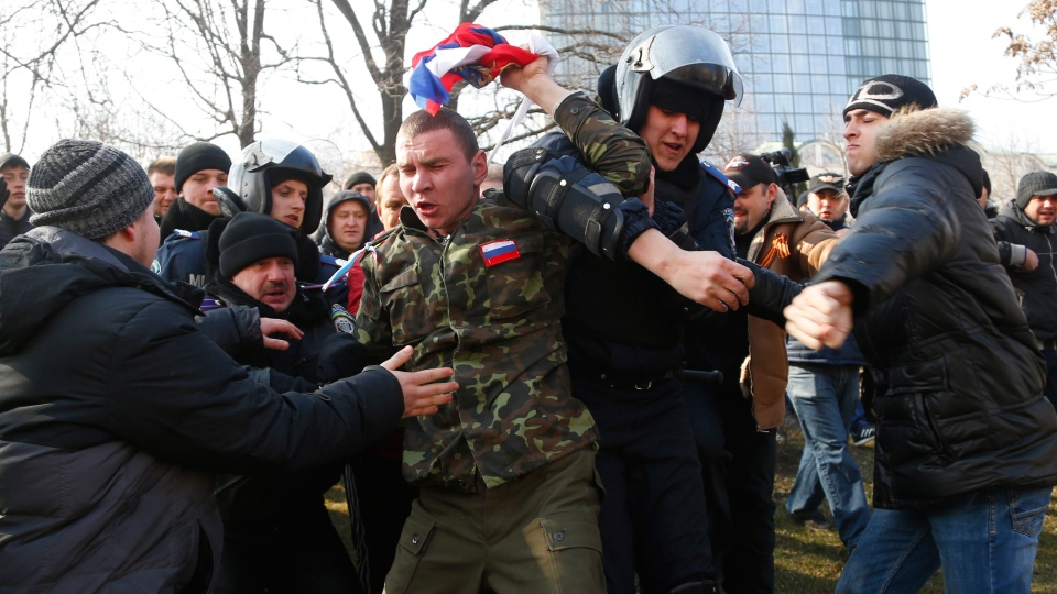Ukrainian police struggle as they detain a demonstrator during a pro Russian rally in Donetsk, Ukraine, Sunday, March 9, 2014. (AP / Sergei Grits)