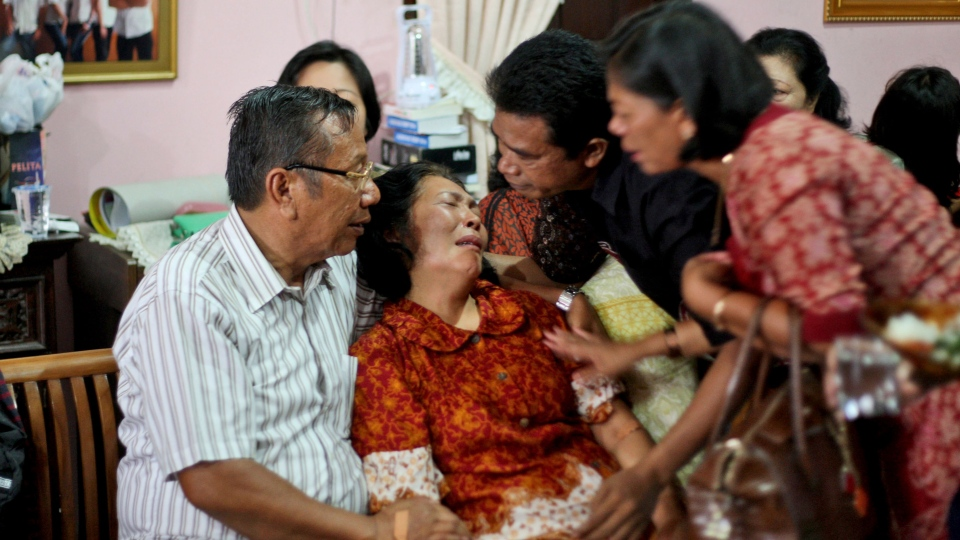 Family members comfort Chrisman Siregar, left, and his wife Herlina Panjaitan, the parents of Firman Siregar, one of the Indonesian citizens registered on the manifest to have boarded the Malaysia Airlines jetliner flight MH370 that went missing over the South China Sea, at their residence in Medan, North Sumatra, Indonesia, Sunday, March 9, 2014. (AP / Binsar Bakkara)