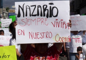 "In this Dec. 12, 2010 file photo, a man holds a sign that reads in Spanish ""Nazario will always live in our hearts,"" referring to La Familia drug cartel leader Nazario Moreno Gonzalez during a demonstration after the government announced he was killed in Apatzingan, Mexico. Years later on Sunday, March 9, 2014, officials say they are trying to determine if a man killed in an early morning shootout is Moreno. (AP / Primera Plana, File)"