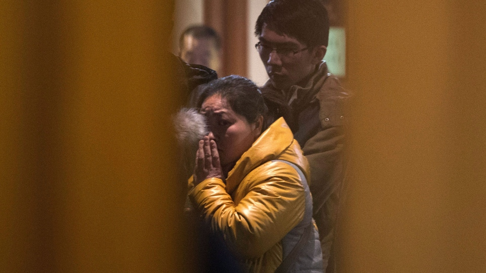 A Chinese relative of passengers aboard a missing Malaysia Airlines plane looks out from a hotel room for relatives or friends of passengers aboard the missing airplane in Beijing, China Monday, March 10, 2014. (AP / Andy Wong)