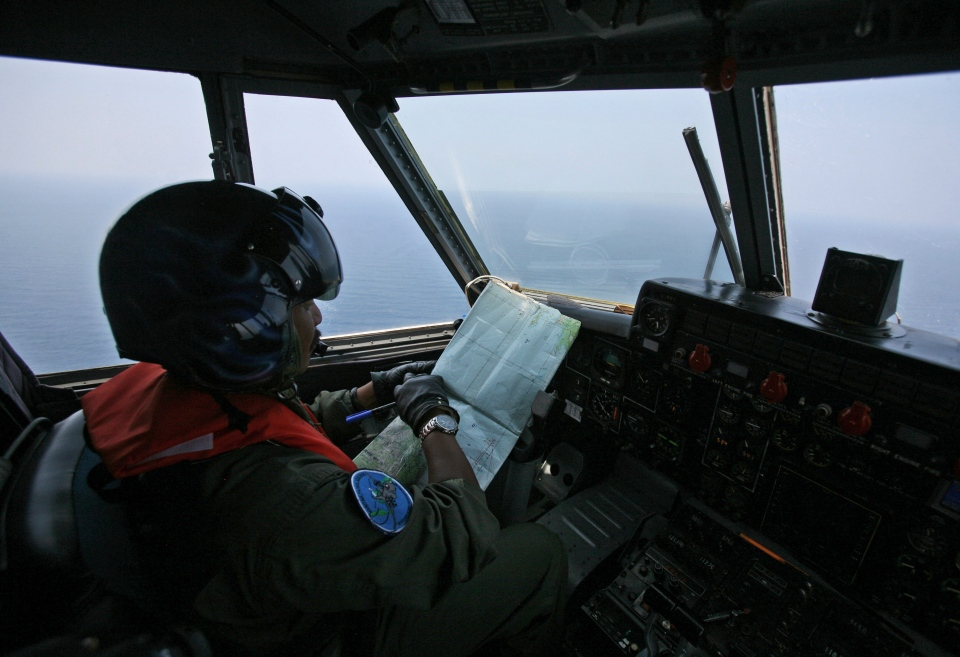 An Indonesian Navy pilot checks his map during a search operation for the missing Malaysian Airlines Boeing 777 over the waters bordering Indonesia, Malaysia and Thailand near the Malacca straits on Monday, March 10, 2014. (AP / Binsar Bakkara)