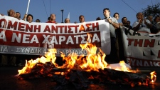 Demonstrators burn copies of emergency tax notices during a protest by the Communist-backed labor union on Wednesday, Sept. 28, 2011. (AP / Petros Giannakouris)
