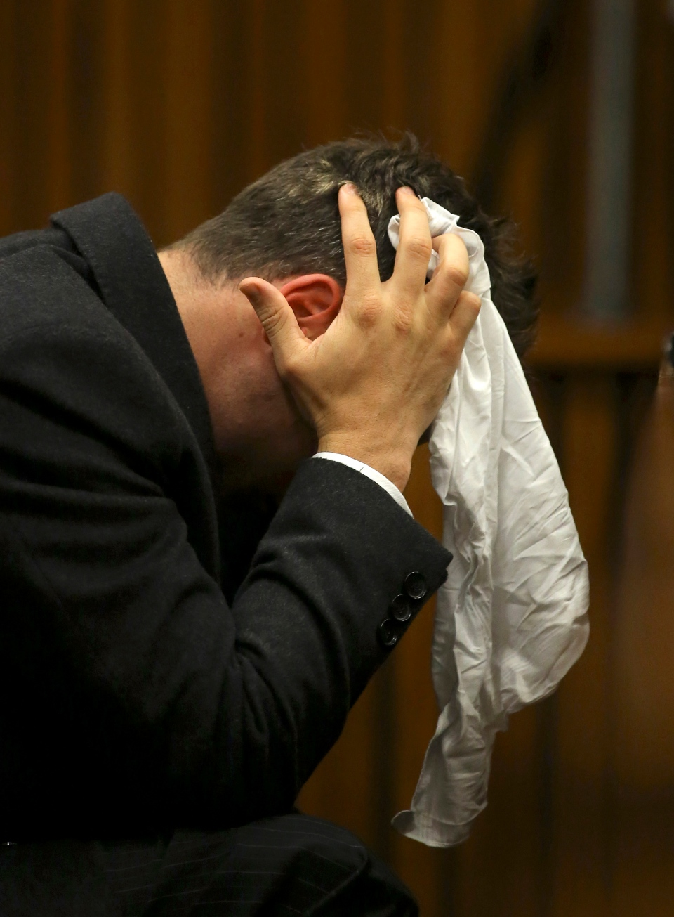 Oscar Pistorius covers his head with a handkerchief after he had reached for a bucket at his feet while listening to cross questioning about the events surrounding the shooting death of his girlfriend Reeva Steenkamp, in his second week in court during his trial in Pretoria, South Africa, Monday, March 10, 2014. (AP / Siphiwe Sibeko)