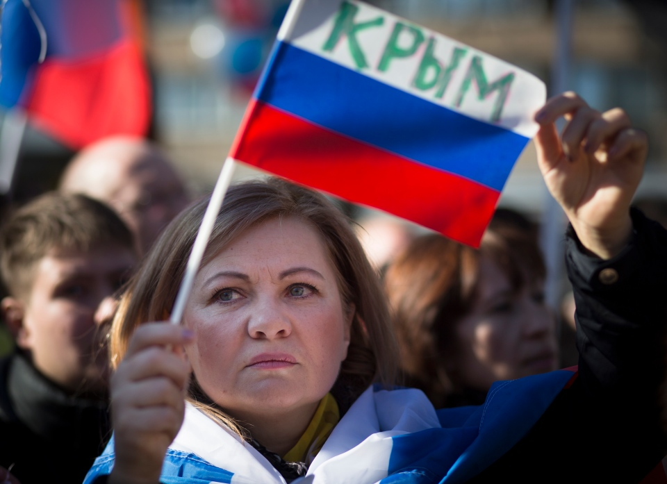 A woman holds a Russian flag with the word reading Crimea as about 1,000 demonstrators gathered to support Russians in Crimea in Moscow, Russia, Monday, March 10, 2014. (AP Photo/Alexander Zemlianichenko)