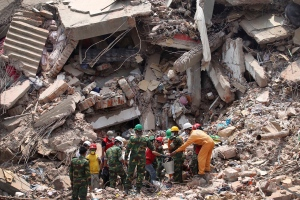 Workers try to release two bodies trapped in the rubble of collapsed Rana Plaza garment factory building in Savar, near Dhaka, Bangladesh, April 30, 2013. (AP / Wong Maye-E)