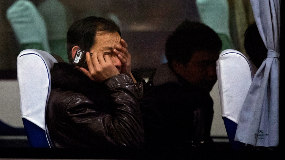 A relative of Chinese passengers aboard missing Malaysia Airlines Flight MH370 rubs his eyes as he talks on his mobile phone while waiting on a bus at a hotel in Beijing, Monday, March 10, 2014. (AP / Alexander F. Yuan)