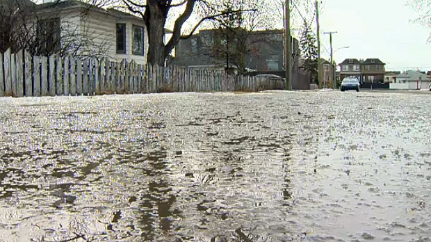 A huge puddle takes up most of the road in the intersection of 1Ave. and 18 St. N.W.
