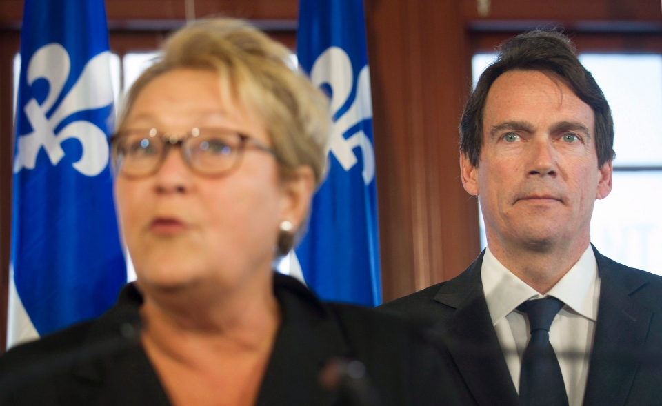 Parti Quebecois leader Pauline Marois speaks to reporters as Pierre Karl Peladeau looks on during a press conference in Saint Jerome, Que., Sunday, March 9, 2014, announcing him as the PQ candidate for that riding on day five of the Quebec provincial election campaign. (Graham Hughes / THE CANADIAN PRESS)