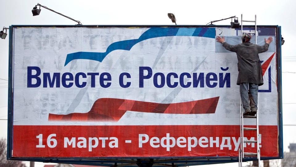 "A man pastes a poster advertising the referendum in Crimea that reads ""Together with Russia! March 16 - Referendum!"" in Simferopol, Ukraine, Monday, March 10, 2014. (AP / Vadim Ghirda)"