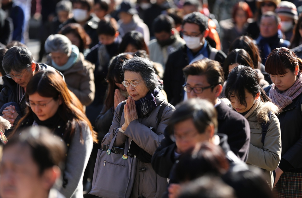 People observe a moment of silence at 2:46 p.m. in Tokyo Tuesday, March 11, 2014, three years after a massive earthquake and tsunami struck northeastern Japan. Japan marked the third anniversary on Tuesday of a devastating disasters that left nearly 19,000 people dead or missing. (AP/Eugene Hoshiko)
