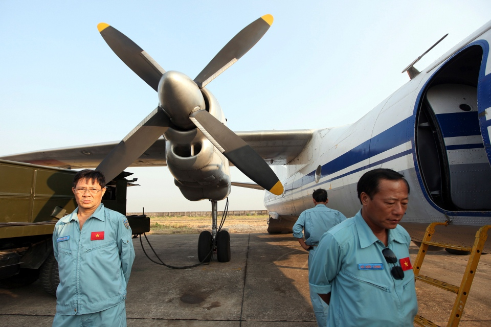 Cabin crew of Vietnam Air Force's AN26 aircraft waits at a base near Tan Son Nhat airport, Hochiminh city before a search operation for the missing Malaysian Airlines Boeing 777 over the seas between Malaysia and Vietnam Tuesday, March 11, 2014. (AP / Na Son Nguyen).