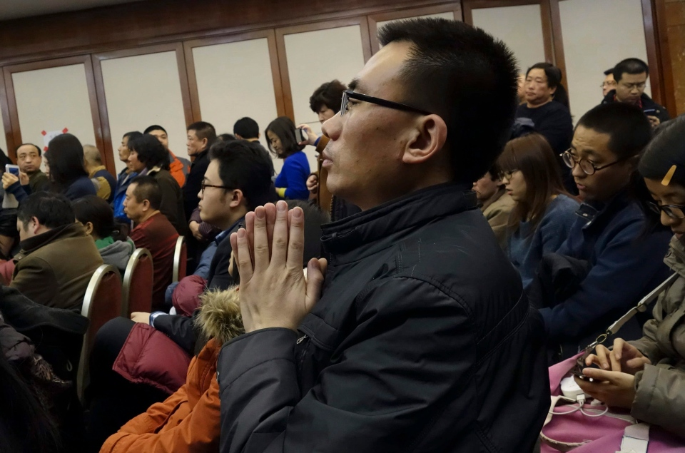 A relative of Chinese passengers aboard missing Malaysia Airlines Flight MH370 prays at a gathering with other passenger families in a hotel in Beijing, China, Monday March 10, 2014. (AP)