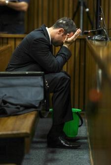 Oscar Pistorius covers his face in Pretoria court