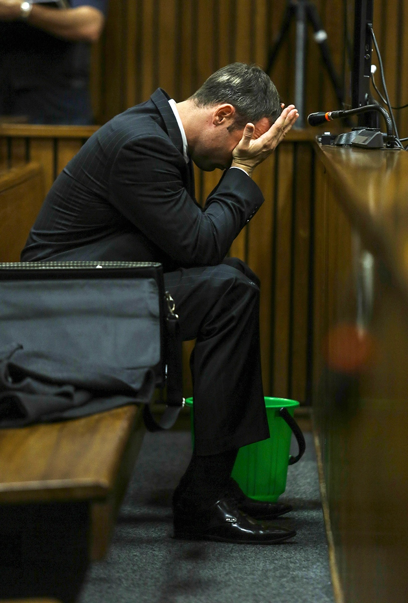 With a bucket on the floor nearby, Oscar Pistorius covers his face with his hands as he listens to cross questioning about the events surrounding the shooting death of his girlfriend Reeva Steenkamp, in court during his trial in Pretoria, South Africa, Tuesday, March 11, 2014. (AP / Kevin Sutherland)