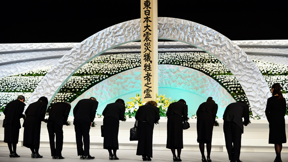 Relatives of victims of the March 11, 2011 earthquake and tsunami bow to the altar as they offer chrysanthemums for the victims of the disasters at the national memorial service in Tokyo, Japan, Tuesday, March 11, 2014. (AP / Franck Robichon)