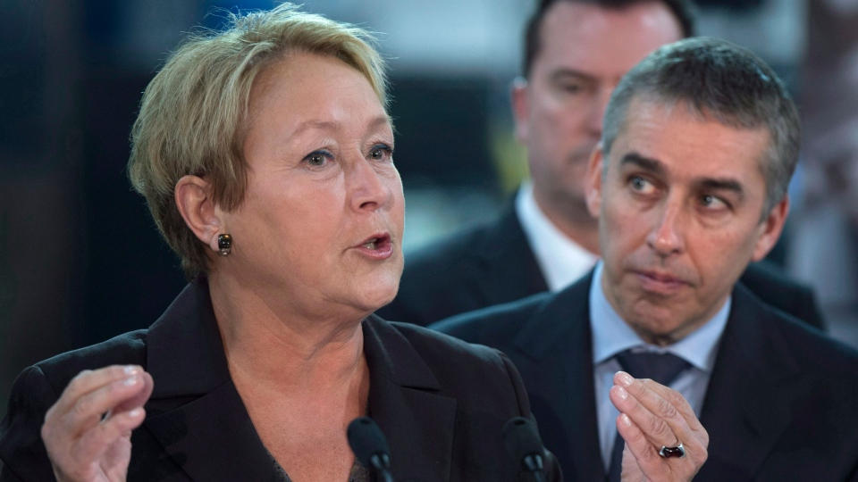 PQ leader Pauline Marois responds to a question as Finance Minister Nicolas Marceau looks on during a campaign stop Monday, March 10, 2014 in Saint-Bruno-de-Montarville, Que. (Paul Chiasson / THE CANADIAN PRESS)