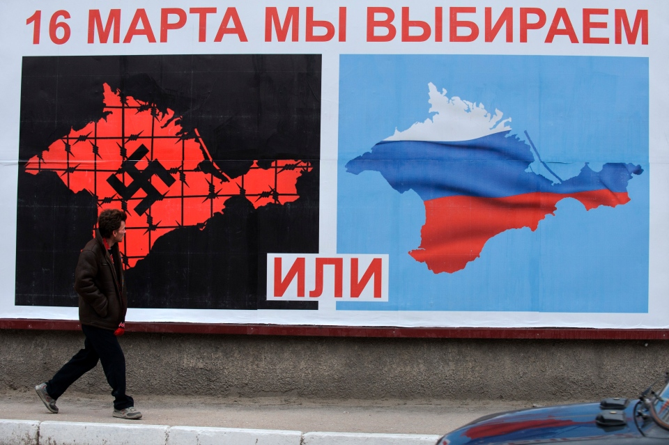 "A man walks past a poster reading ""On March 16 We Vote Or,"" in Sevastopol, Crimea, Ukraine, Tuesday, March 11, 2014. (AP / Andrew Lubimov)"
