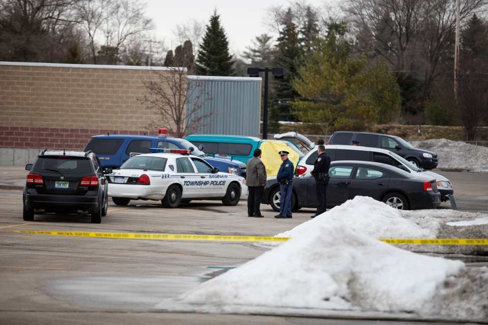 Police gather together in the parking lot of Saginaw Township Wal-Mart, Tuesday, March 11, 2014. Police found a 1995 GMC Sierra that matches the description of Terry Trafford's vehicle. Police found a body in the truck but have not yet identified the person. (AP / The Saginaw News, Neil Barris)