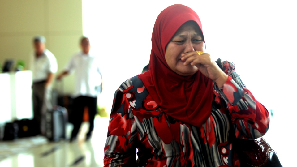 A relative cries as she arrives at a hotel designated as a holding area for family members of passengers on board the missing Malaysia Airlines jetliner MH370, Wednesday, March 12, 2014, in Sepang, Malaysia. (AP / Joshua Paul)