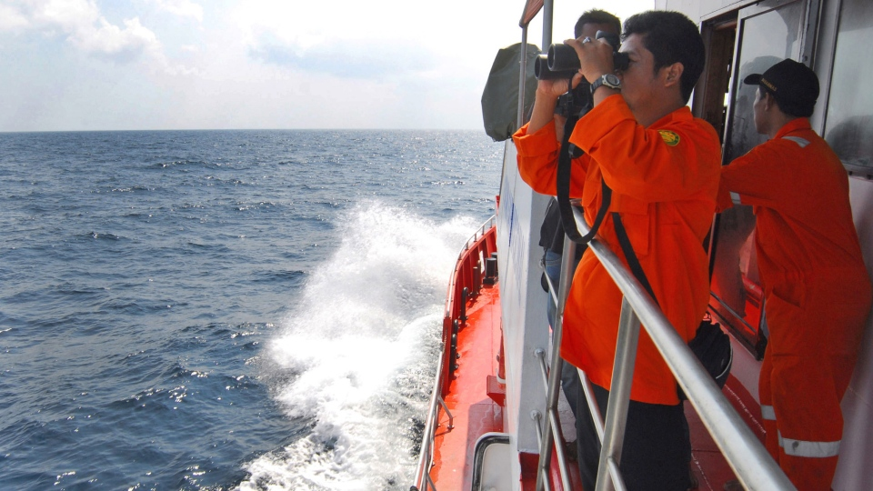 A member of Indonesian National Search and Rescue Agency uses a binocular to scan the horizon during a search operation for the missing Malaysia Airlines Boeing 777 conducted on the waters of the Strait of Malacca off Sumatra island, Indonesia, Wednesday, March 12, 2014. (AP / Heri Juanda)