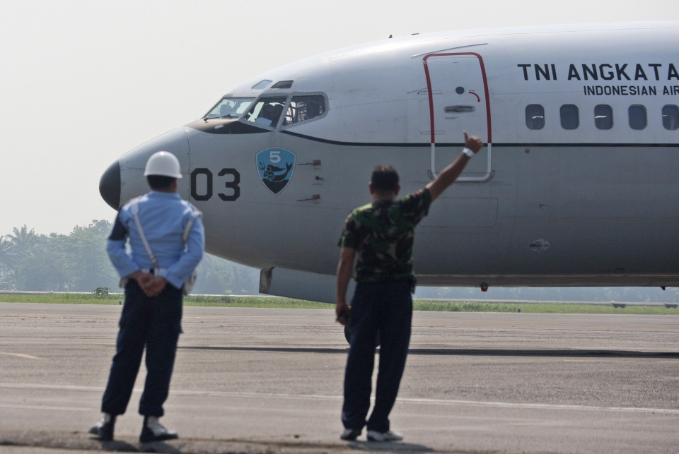 Indonesian Air Force ground crew gestures to the pilots of a Boeing 737 'Surveiller' maritime patrol aircraft of the 5th Air Squadron 'Black Mermaids' prior to a search operation for the missing Malaysia Airlines Boeing 777 that will be conducted the Strait of Malacca, at Suwondo air base in Medan, North Sumatra, Indonesia, Wednesday, March 12, 2014. (AP / Binsar Bakkara)