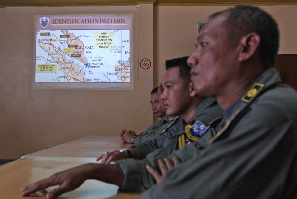 An operation map is displayed on the wall as Indonesian Air Force personnel listen to a briefing following to a search mission for the missing Malaysia Airlines Boeing 777 that was conducted over the Strait of Malacca, at Suwondo air base in Medan, North Sumatra, Indonesia, Wednesday, March 12, 2014. (AP / Binsar Bakkara)