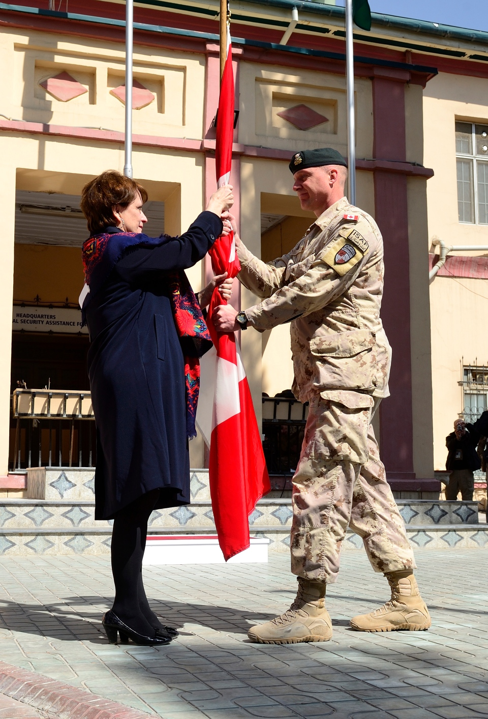 Maj.-Gen. Dean Milner, last Commander of the Canadian Contribution to the Training Mission in Afghanistan, hands over the Canadian flag to Deborah Lyons, Canada's ambassador to the Islamic Republic of Afghanistan, as a symbol of the continued Canadian support to Afghanistan during the flag lowering ceremony, Wednesday, March 12, 2014. (Master Cpl. Patrick Blanchard / Canadian Forces Combat Camera)
