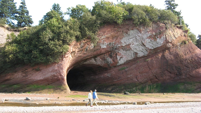 A couple walks on the ocean floor at low tide to view the caves carved in the red sandstone by the Bay of Fundy, N.B., in this undated photo. (Kevin Bissett / THE CANADIAN PRESS)
