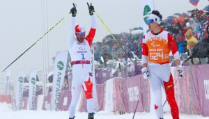 Brian Mckeever of Canada, left, celebrates his gold medal in men's cross country 1km sprint, visually impaired event at the 2014 Winter Paralympic, Wednesday, March 12, 2014, in Krasnaya Polyana, Russia. (AP Photo/Dmitry Lovetsky)
