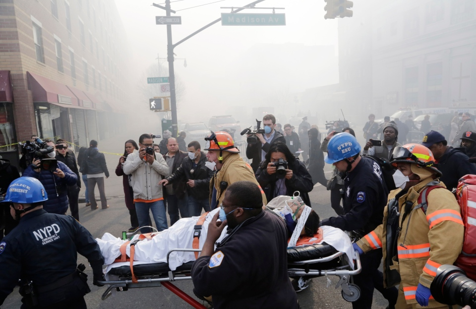 Rescue workers remove an injured person on a stretcher after a possible explosion and building collapse in the East Harlem neighborhood of New York, Wednesday, March 12, 2014. (AP / Mark Lennihan)