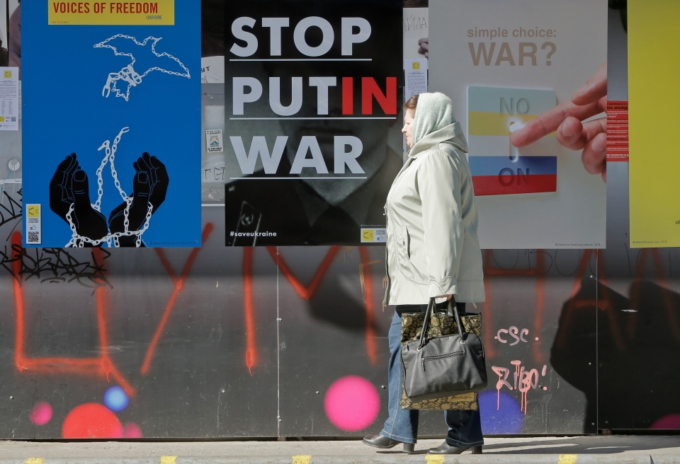 A woman passes by the posters during the International poster campaign to support Ukraine in center Kyiv, Ukraine, Wednesday, March, 12, 2014. (AP / Efrem Lukatsky)