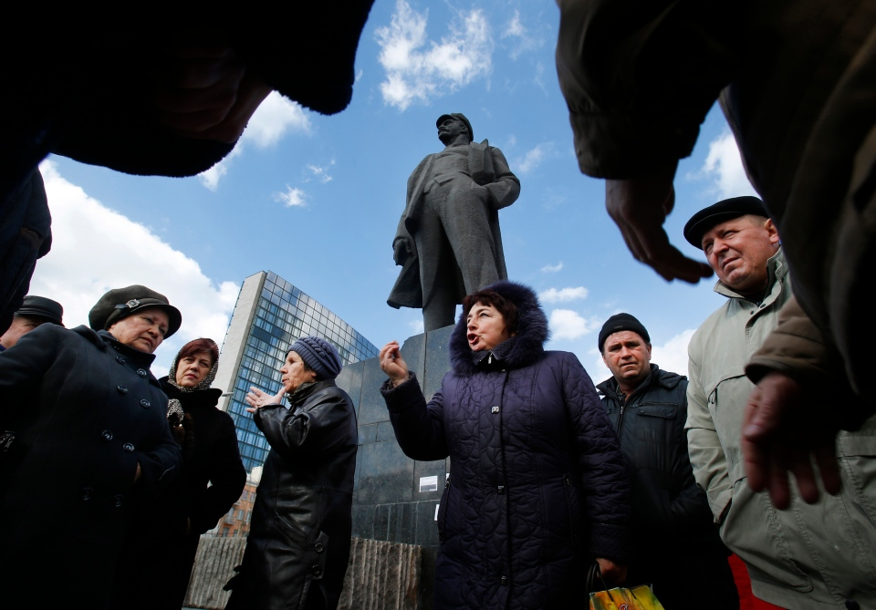People talk about developments in Ukraine at a central square next to a statue of Soviet revolutionary leader Vladimir Lenin in Donetsk, Ukraine, Wednesday, March 12, 2014. (AP / Sergei Grits)