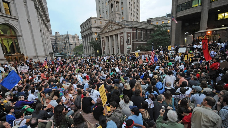 Protesters sit in the plaza of Police Headquarters, Friday, Sept. 30, 2011, in New York. (AP / Louis Lanzano)