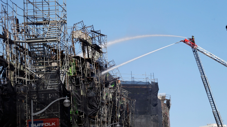 Firefighters continue to work a day after a structure fire in the Mission Bay neighborhood in San Francisco on Wednesday, March 12, 2014. (AP / Marcio Jose Sanchez)