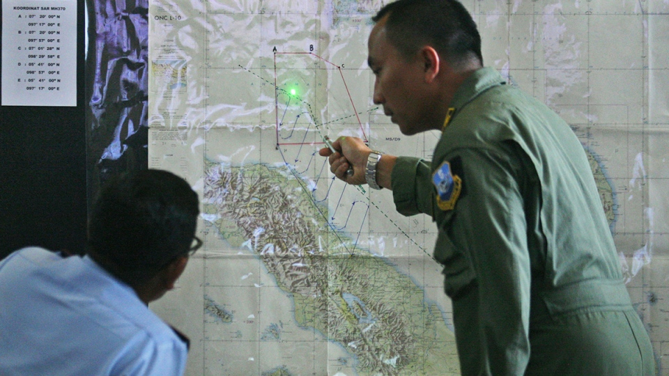 Indonesian Air Force officers examine a map of the Malacca Strait during a briefing following a search operation for the missing Malaysia Airlines Boeing 777, at Suwondo air base in Medan, North Sumatra, Indonesia, Wednesday, March 12, 2014. (AP / Binsar Bakkara)