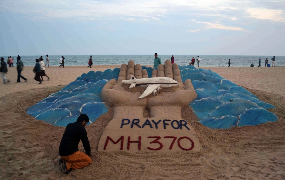 Sand artist Sudarshan Pattnaik creates a sculpture depicting the missing Malaysian Airlines aircraft on the beach in Puri, India, Wednesday, March 12, 2014. (AP Photo)