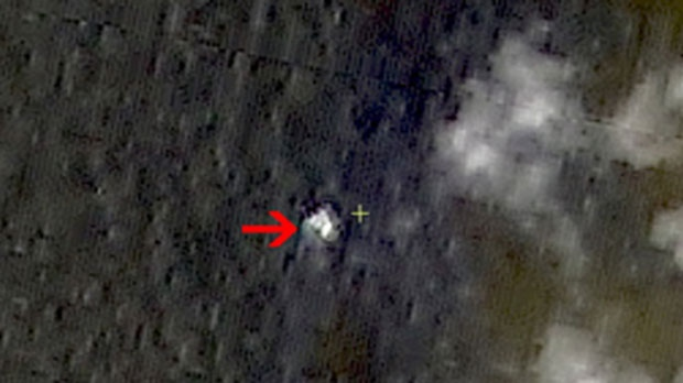 Floating objects are seen at sea next to the red arrow which was added by the source on March 9, 2014. (Chinese State Administration of Science / Technology and Industry for National Defense)