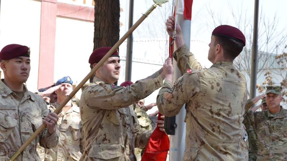 Master Cpl. Daniel Choong, left, Cpl. Harry Smiley (centre) and Cpl . Gavin Early, right, take down the Canadian flag for the last time in Afghanistan, Wednesday, March 12, 2014. (Murray Brewster / THE CANADIAN PRESS)