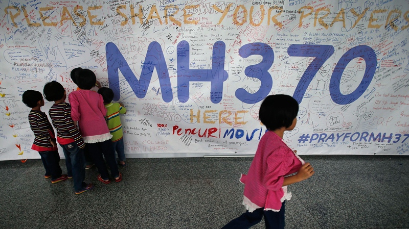 Children read messages and well wishes displayed for all involved with the missing Malaysia Airlines jetliner MH370 on the walls of the Kuala Lumpur International Airport, Thursday, March 13, 2014 in Sepang, Malaysia. (AP Photo/Wong Maye-E)