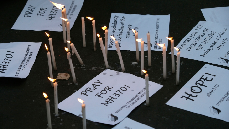 Candles are lit next to messages as students express hope and solidarity for the passengers aboard the missing Malaysian Airlines plane in Manila, Philippines, Thursday, March 13, 2014. (AP / Bullit Marquez)