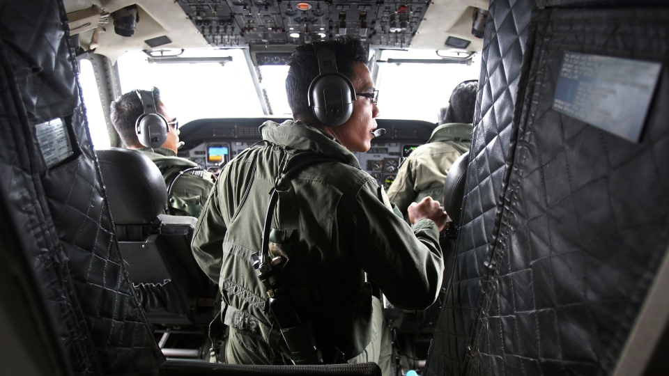 Pilots of a Royal Malaysian Air Force CN-235 aircraft manage their plane during a search and rescue operation for the missing Malaysia Airlines plane over the waters at Malacca straits, Malaysia, Thursday, March 13, 2014. (AP / Lai Seng Sin)