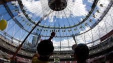 People look up at the new retractable roof being installed at BC Place during a public preview on Jul. 31, 2011. The stadium will play host to this year's Grey Cup and is scheduled to re-open on Sept. 30, 2011 when the CFL's BC Lions host the Edmonton Eskimos. (CP/Darryl Dyck)