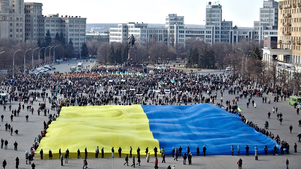 Pro-Ukrainian activists demonstrate a huge yellow-and-blue Ukrainian flag during a rally in support of Ukraine's territorial integrity in the eastern city of Kharkiv, Ukraine, Thursday, March 13, 2014. (AP / Segey Kozlov)