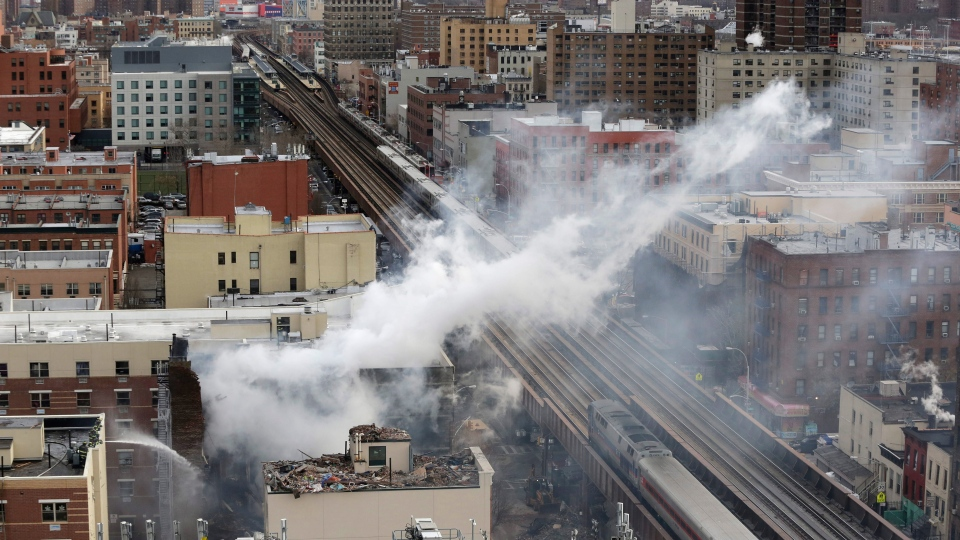 Firefighters, lower left, pour water on the site of a building explosion, as a Metro-North commuter train, right, passes the site on in New York, Thursday, March 13, 2014. (AP / Mark Lennihan)
