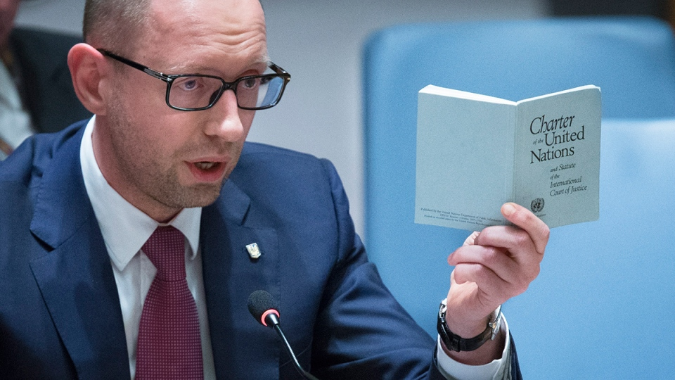Ukrainian interim Prime Minister Arseniy Yatsenyuk speaks as he holds a copy of the United Nations charter during an UN Security Council meeting on the Ukraine crisis, at the United Nations Headquarters, Thursday, March 13, 2014. (AP / John Minchillo)