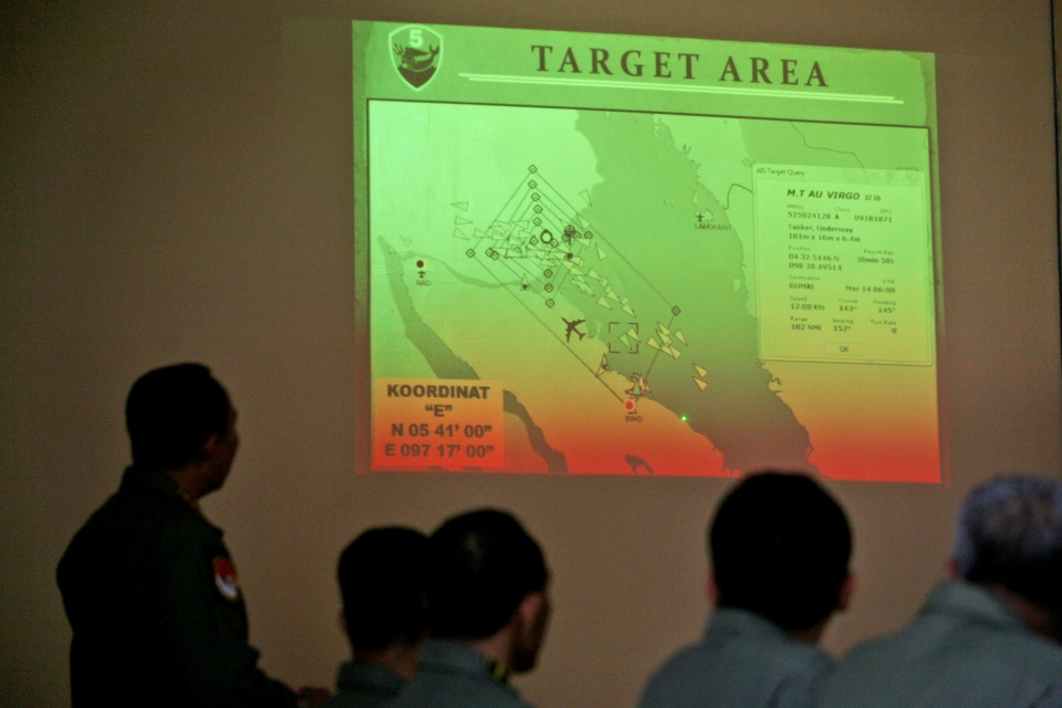 Indonesian Air Force officers examine the projection of a map that shows their operation area over the Strait of Malacca during a briefing following a search mission for the missing Malaysia Airlines Boeing 777, at Suwondo air base in Medan, North Sumatra, Indonesia, Thursday, March 13, 2014. (AP / Binsar Bakkara)