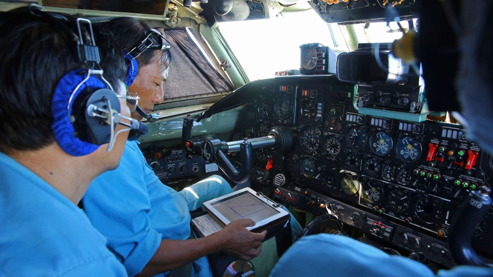 Cabin crews of Vietnam Air Force are seen onboard a flying AN-26 Soviet made aircraft during a search operation for the missing Malaysia Airlines flight MH370 plane over the southern sea between Vietnam and Malaysia, Friday, March 14, 2014. (AP / Na Son Nguyen)